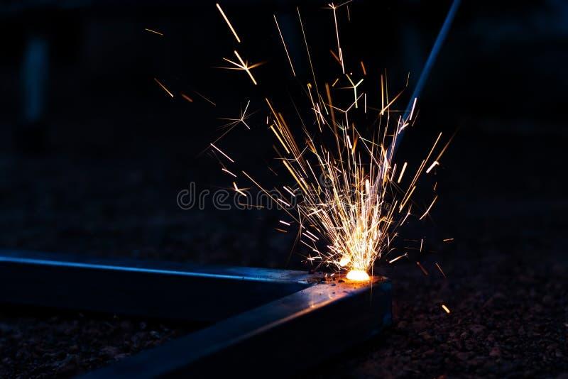 Foyer de technicien sur le procédé de soudure sur la lumière d'étincelle avec l'équipement photo libre de droits