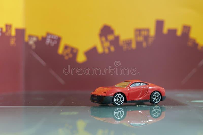 Foyer sélectif de berline de jouet rouge de voiture sur le fond de ville de tache floue photos stock