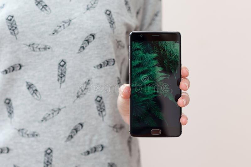 Foyer sélectif, effet de film Jeune femme tenant le téléphone portable avec l'espace de copie, montrant son écran vide noir à l'a photographie stock libre de droits