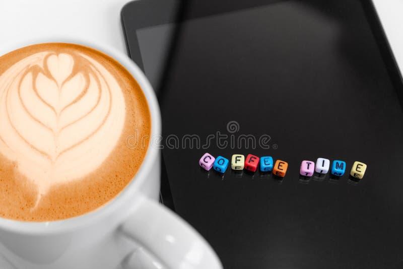 Foyer sélectif sur des blocs de cube en lettres avec des concepts de temps de café Café chaud écumeux avec l'art de feuille photos stock