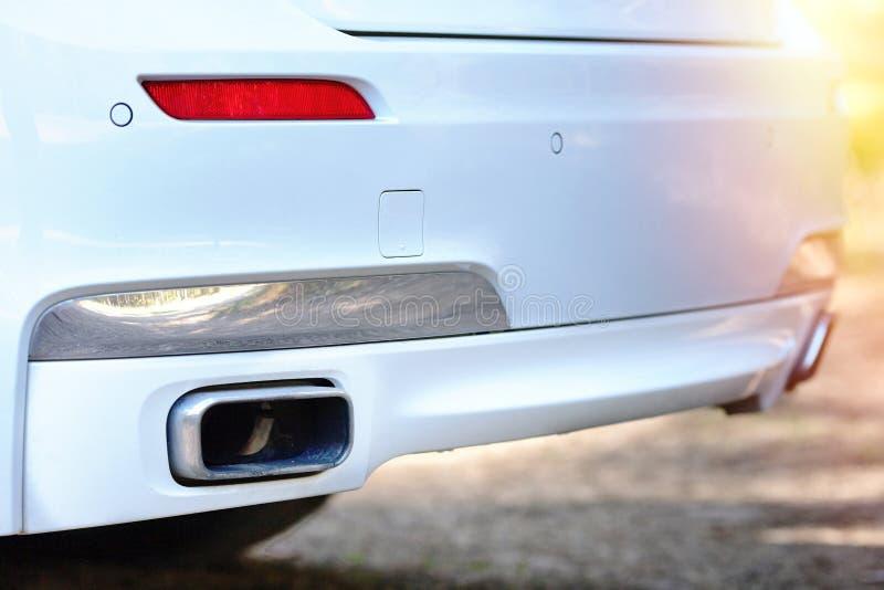 Foyer sélectif sur le pare-chocs se garant de pot d'échappement de capteur à l'arrière de fin de butoir de voiture luxueuse blanc image stock