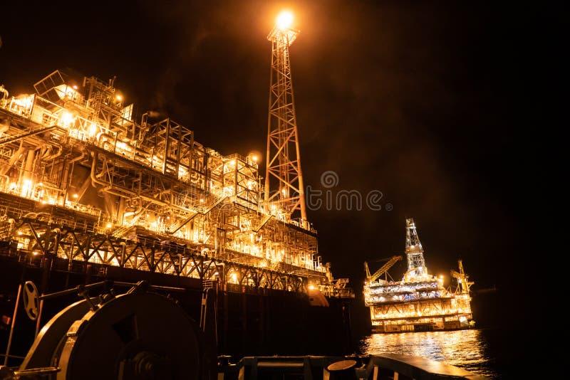 FPSO在石油平台船具附近的罐车船在晚上 近海油和煤气产业 库存照片