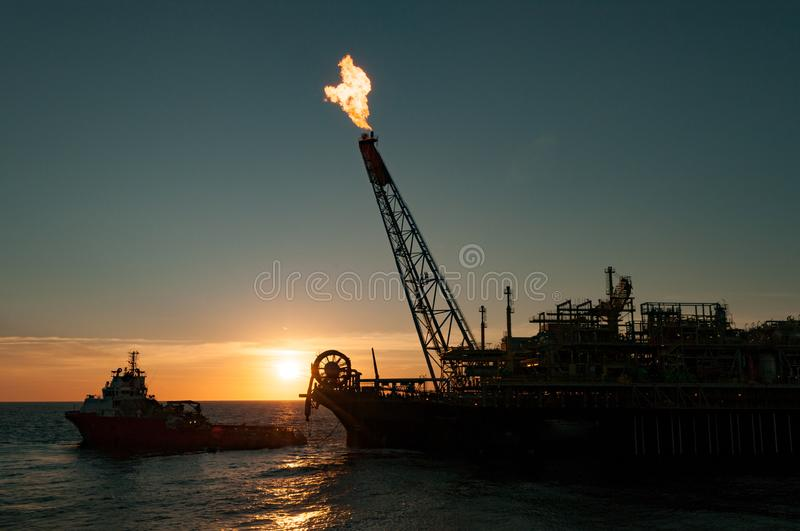 FPSO oil rig and Supply vessel. FPSO oil rig vessel silhouette with gas flare, with supply vessel. Back light view, sunset/sunrise time royalty free stock image