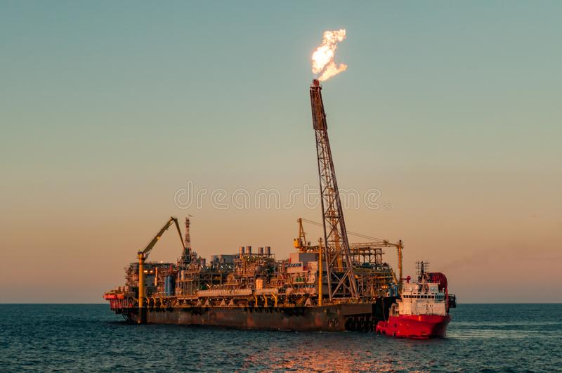 FPSO oil rig and Supply vessel. FPSO oil rig vessel silhouette with gas flare, at sunset/sunrise time, with a supply vessel ship moored along side, for some royalty free stock image