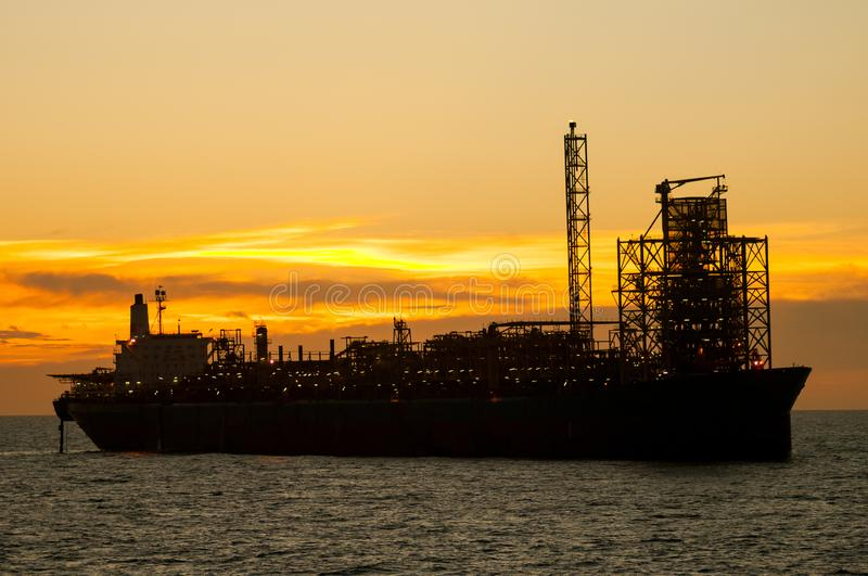 FPSO oil rig vessel at sunset/sunrise. FPSO oil rig vessel silhouette at sunset/sunrise, floating at the ocean. Campos Basin, Rio de Janeiro, Brazil stock photos