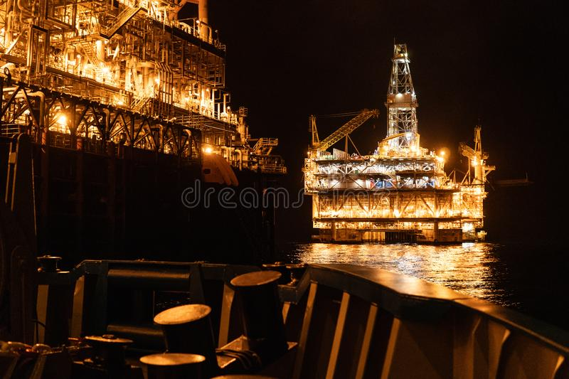 FPSO tanker vessel near Oil platform Rig at night. Offshore oil and gas industry royalty free stock images