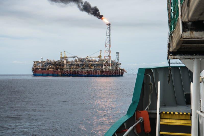 FPSO-tankfartygskyttel nära oljeplattformplattformen Frånlands- fossila bränslenbransch arkivbilder