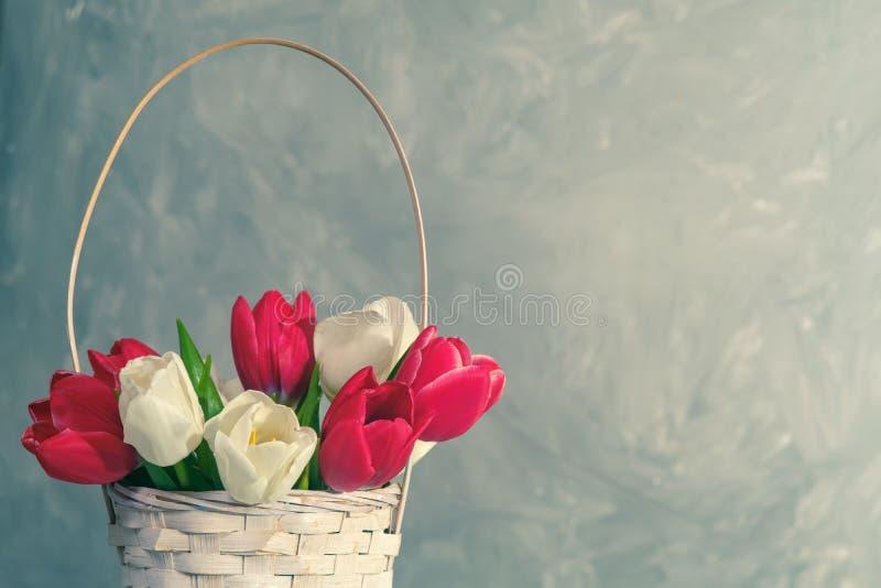 Frühlingsblumenstrauß von Tulpen im Korb auf Weinlesehintergrund Fahnenschablone mit copyspace für den Tag der Frau oder Mutter,  stockfoto