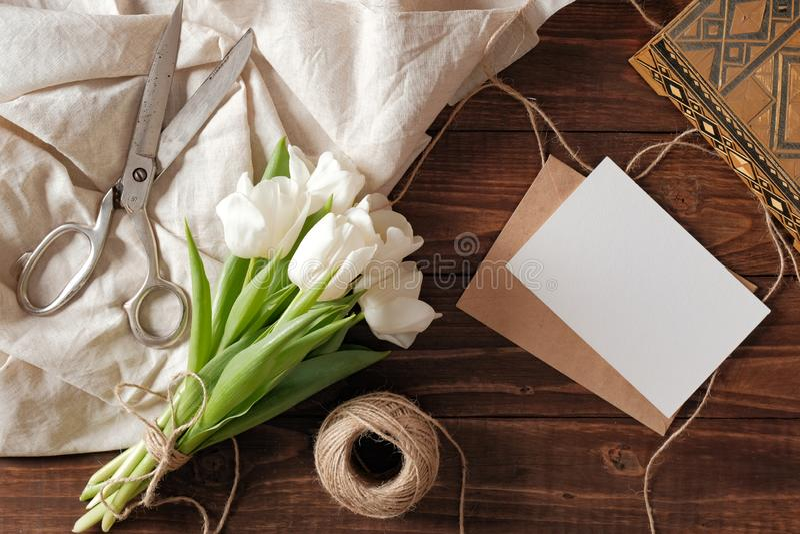 Frühlingsblumenstrauß von weißen Tulpenblumen, Kraftpapier-Umschlag mit leerer Karte, Scheren, Schnur auf rustikalem Holztisch Ho lizenzfreie stockfotos