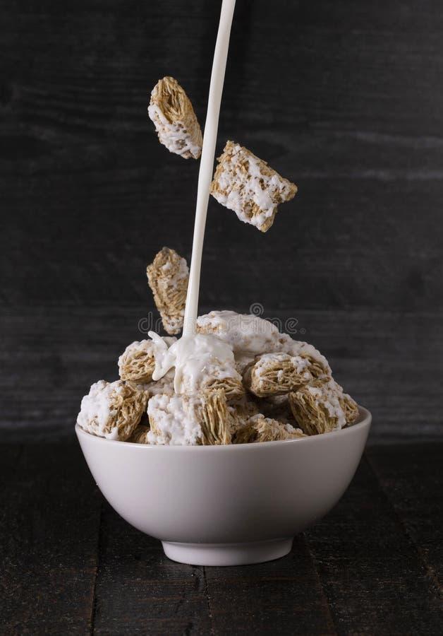 Frühstückskost aus Getreide und Milch, die in eine Schüssel ausgelaufen wird stockfotos