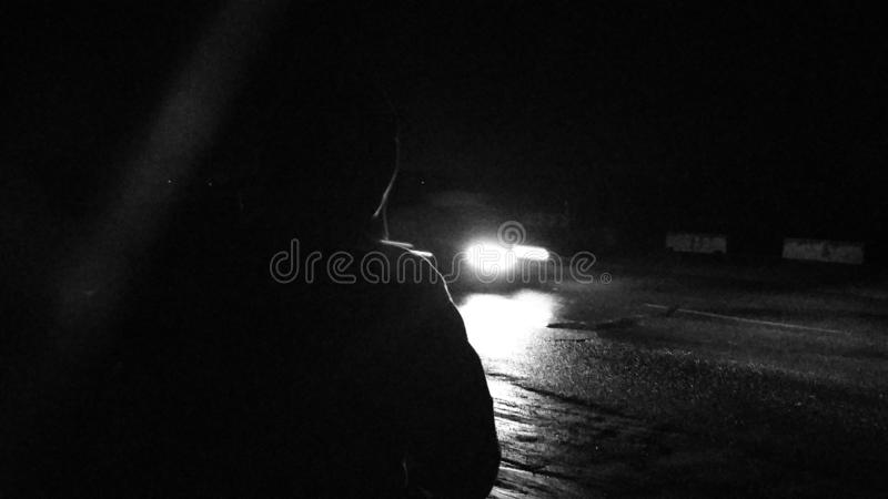 Främling i natten som väntar på en bil arkivbild