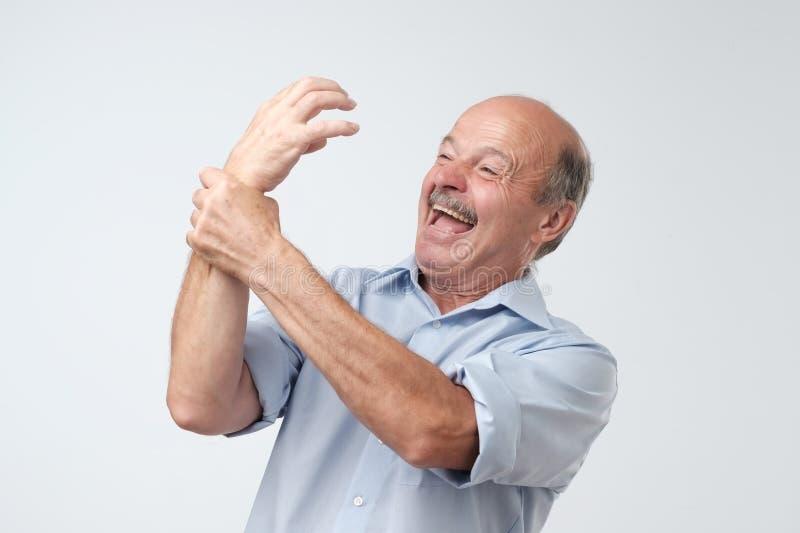 Främmande handsyndrom Mogen man som försöker att kontrollera hans hand royaltyfria foton