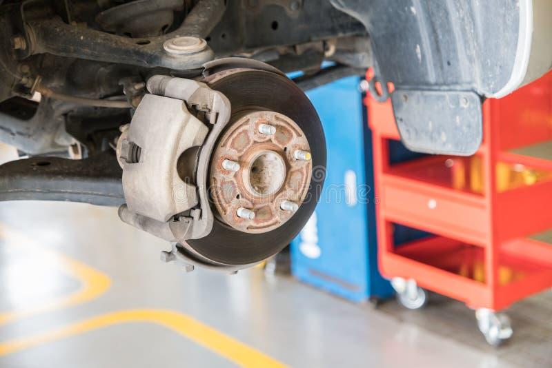 Främre diskettbroms på bilen i process av det nya gummihjulutbytet arkivbild