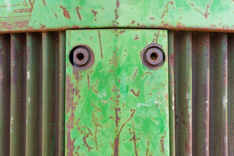 Främre näsa av traktoren för lantgårdutrustning Metallbakgrundsfoto med rost, det curvy metalllufthålet och grön gå i flisor måla royaltyfri foto