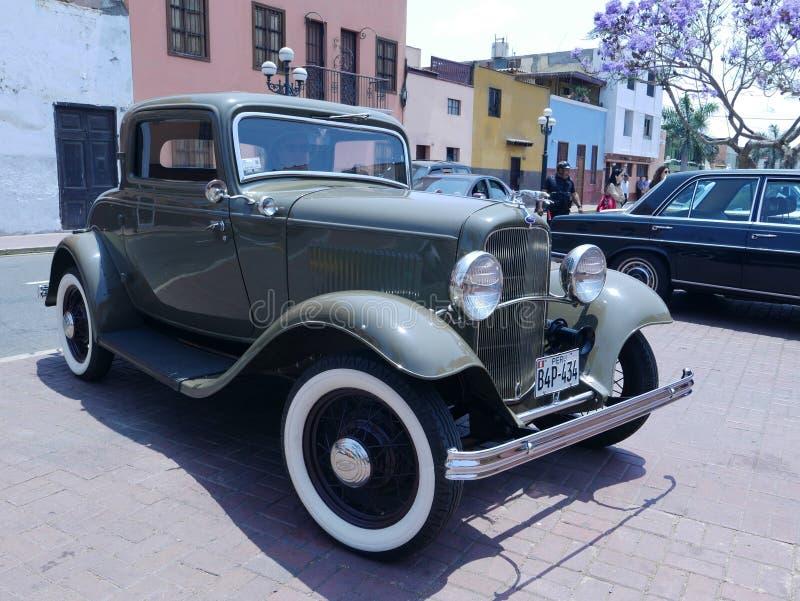 Främre och sidosikt av gröna dörrar för en Ford De Luxe kupé som två ställs ut i Lima royaltyfri fotografi
