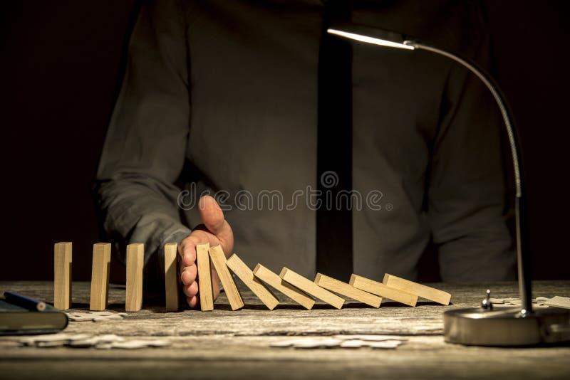 Främre sikt av affärsmannen som stoppar fallande domino med hans hand arkivbild