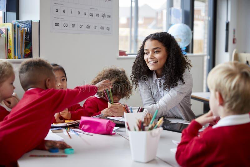 Främre sikt av att le den kvinnliga läraren för begynnande skola som sitter på en tabell i klassrumet med en grupp av skolbarn royaltyfri fotografi