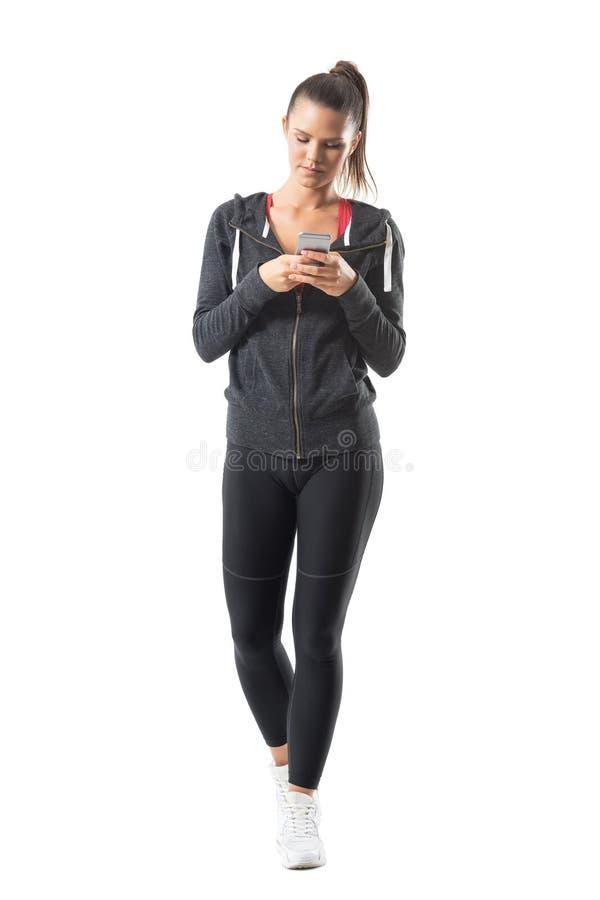 Främre sikt av avkopplad ung sportig passformkvinnamaskinskrivning på mobiltelefonen arkivfoto