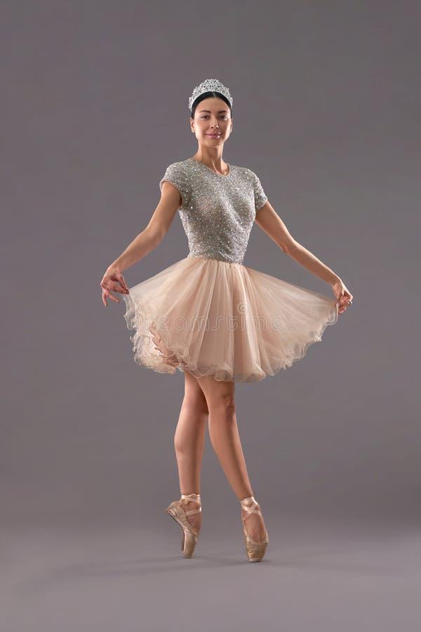 Främre sikt av ballerina som håller klänningen med fingrar i studio royaltyfri fotografi
