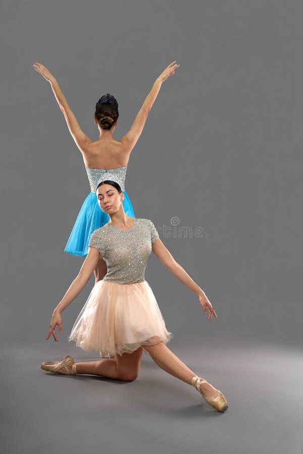 Främre sikt av ballerina som sitter på knä och pekar tår royaltyfria foton