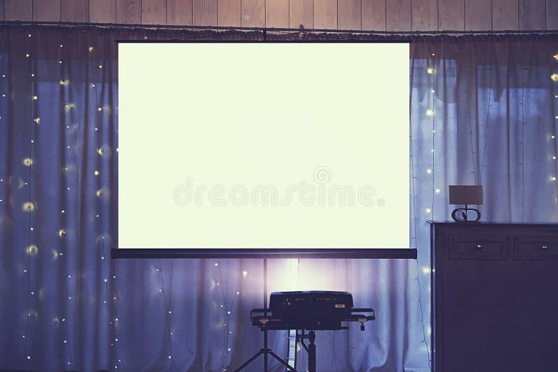 Främre sikt av dekorerat brölloprum med den tomma vita projektorskärmen i mitten Utrustning för video- och slideshowprojektion royaltyfria bilder