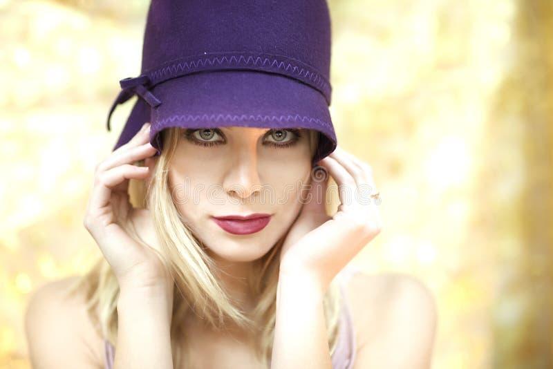 Främre sikt av den blonda kvinnan med den purpurfärgade hatten och blåa ögon royaltyfri fotografi