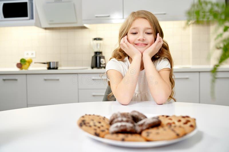 Främre sikt av den härliga flickan som ser smakliga kakor arkivbilder