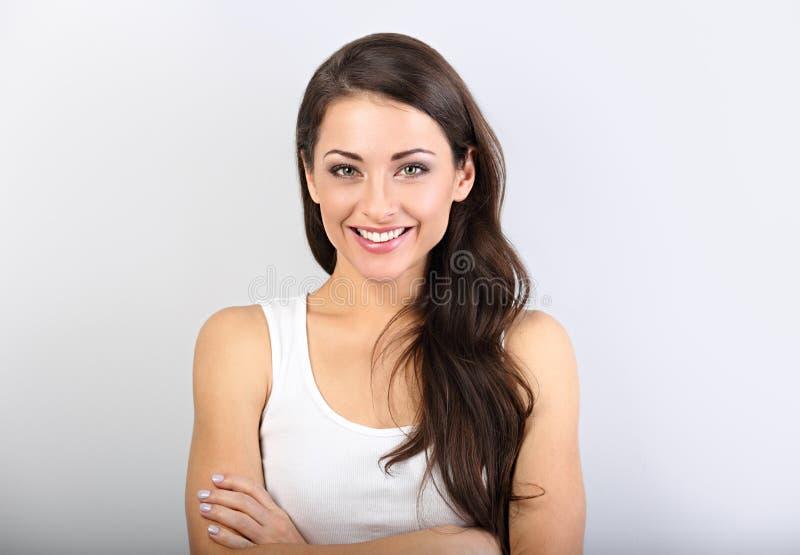 Främre sikt av den härliga kvinnan med näck makeup och sund skenhud som ser med vikta armar royaltyfri fotografi