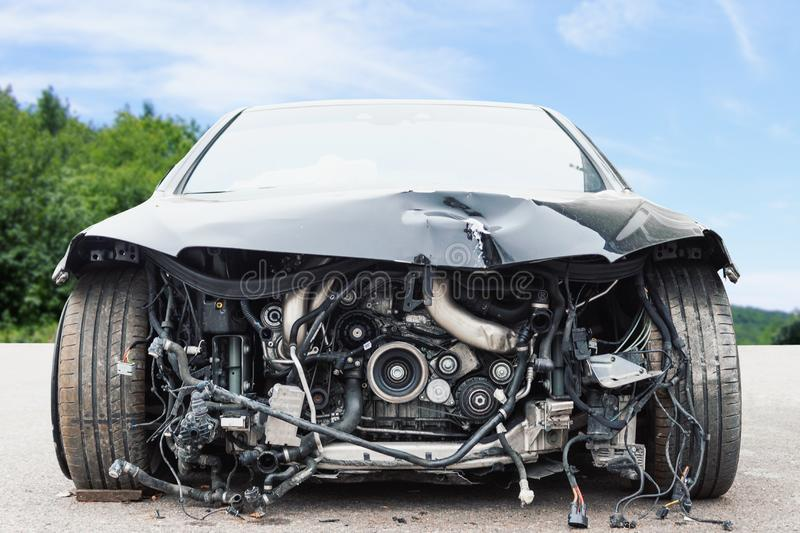 Främre sikt av den kraschade bilen med skadade bildelar på gatan royaltyfri bild