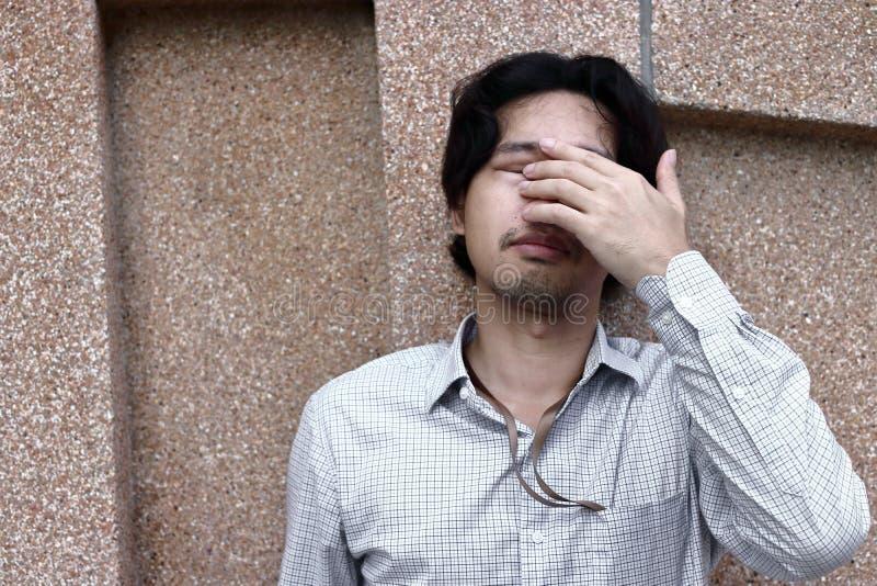 Främre sikt av den ledsna deprimerade unga asiatiska affärsmannen som täcker framsidan och skrik royaltyfria bilder