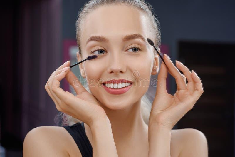 Främre sikt av den lyckliga kvinnan som håller mascara och att posera royaltyfria foton
