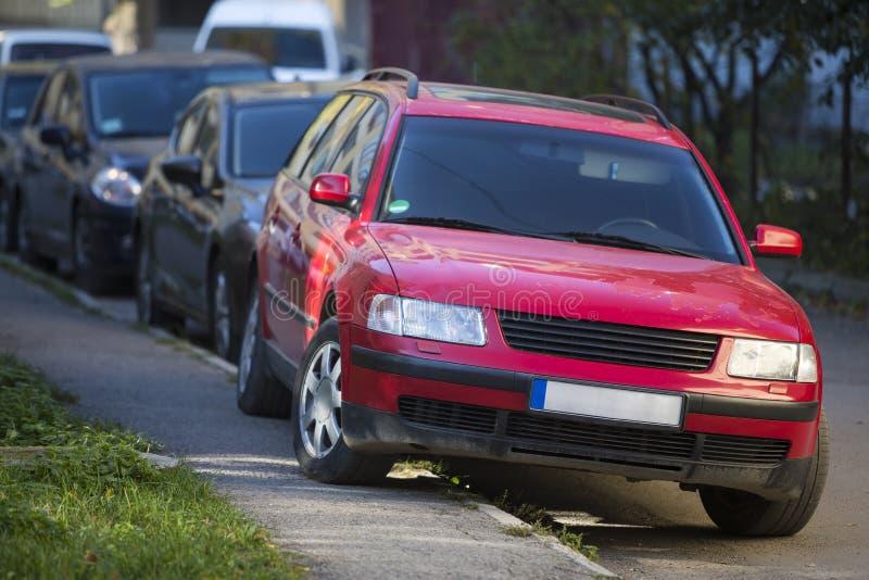 Främre sikt av den röda bilen som delvis parkeras på trottoaren på bakgrund av den långa raden av olika medel längs vägrenen på s royaltyfri fotografi