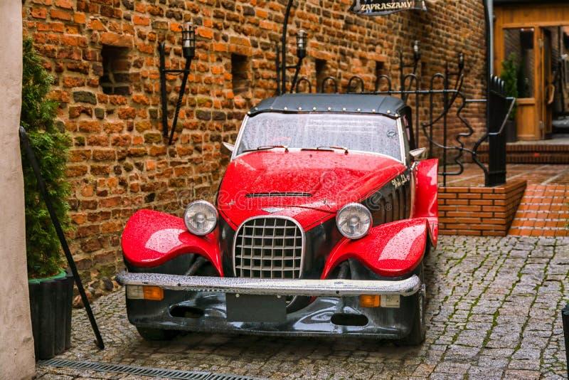 Främre sikt av den röda retro bilen, sikt av den brittiska bilen för röd klassisk tappning i Polen, Olsztyn arkivbild