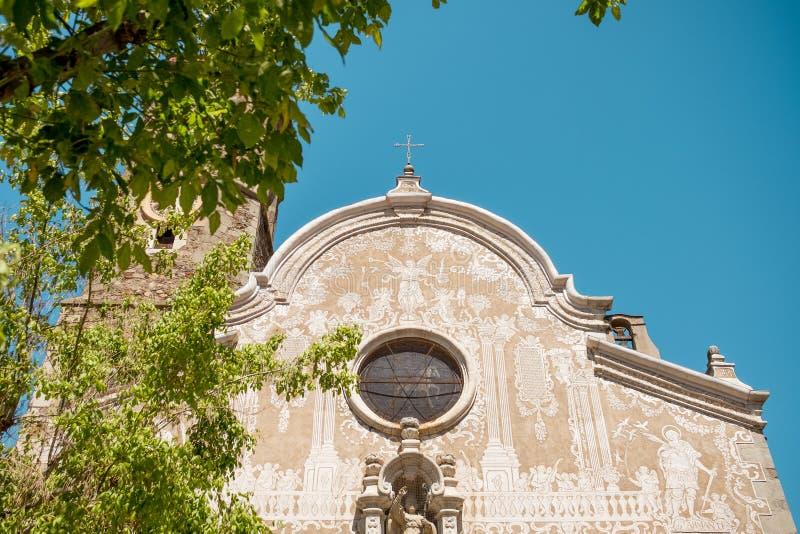 Fr?mre sikt av den san martikyrkan i den lilla catalan staden av Sant Celoni p? en solig sommardag med tr?d och spanska flaggor o arkivbilder
