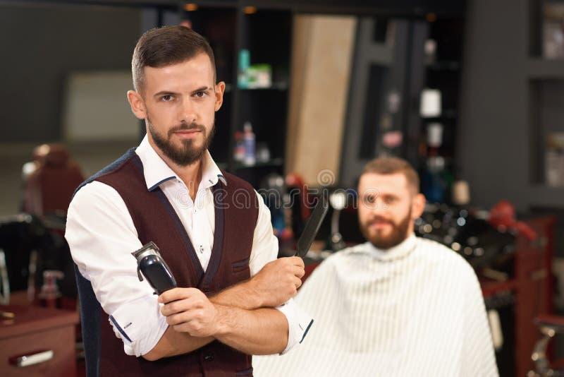 Främre sikt av den stilfulla barberaren med vikta armar royaltyfria bilder