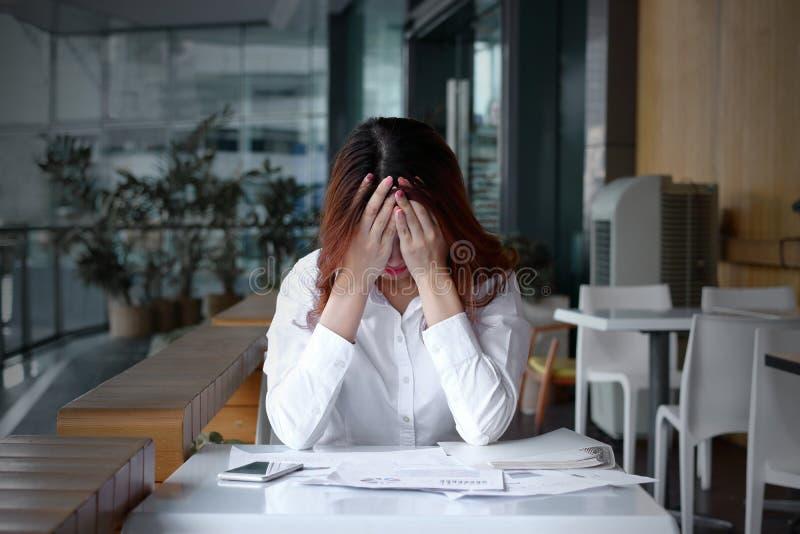 Främre sikt av den stressade frustrerade unga asiatiska framsidan för beläggning för affärskvinna med händer på skrivbordet i reg arkivfoto