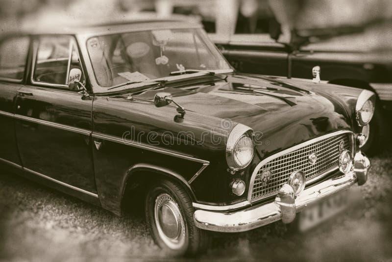 Främre sikt av den svarta bilen för klassisk tappning som parkeras på gräs - retro fotografi royaltyfri fotografi