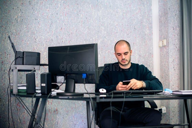 Främre sikt av den unga affärsmannen som i regeringsställning använder mobiltelefonen royaltyfria foton