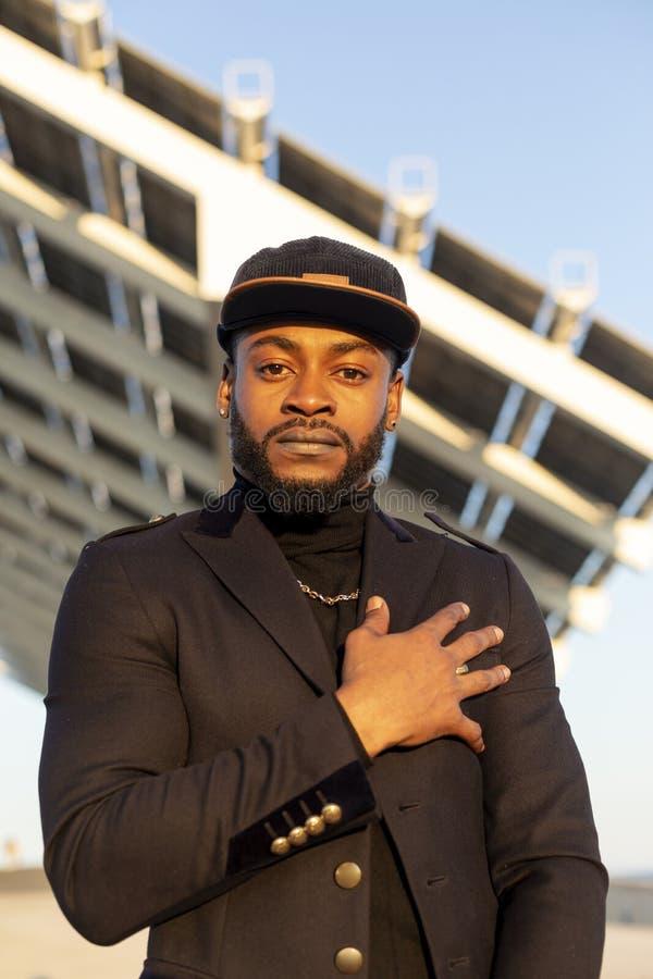 Främre sikt av den unga svarta stilfulla mannen som utomhus står i en solig dag, medan se kameran royaltyfri fotografi