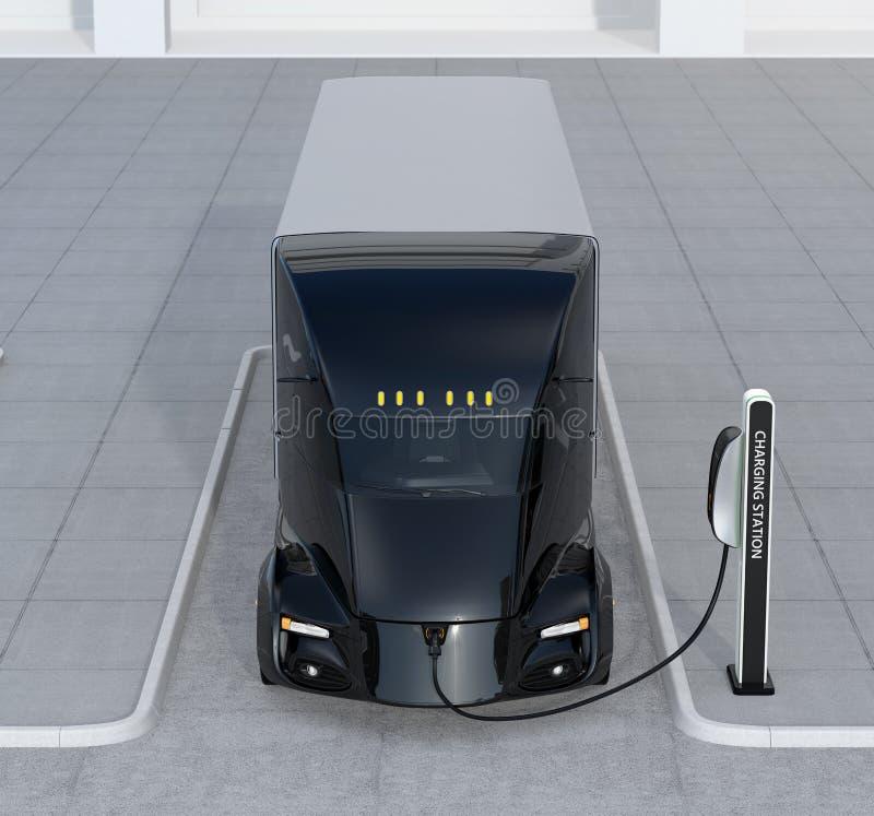 Främre sikt av denkörande elektriska lastbilen som laddar på uppladdningsstationen arkivfoto
