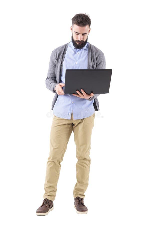Främre sikt av det allvarliga innehavet och att se för affärsman bärbar datordatoren arkivfoto