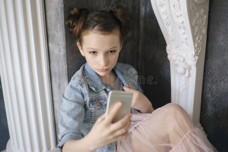 Främre sikt av en allvarlig flicka som kontrollerar ett telefonmeddelande som går på arkivfoton