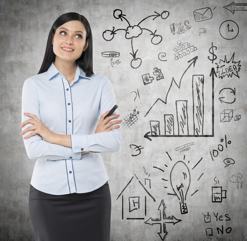 Främre sikt av en fundersam kvinna med korsade händer Ett begrepp av en kläckning av ideer Affärssymboler dras på väggen arkivbild