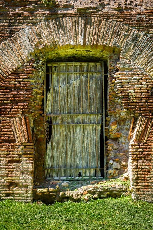 Främre sikt av en gammal forntida riden ut träingångsdörr och den orange tegelstenväggen royaltyfria bilder