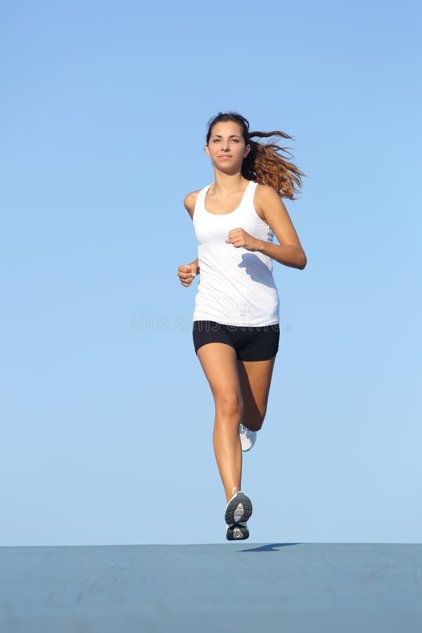 Främre sikt av en härlig idrottskvinnaspring in mot kamera arkivbild