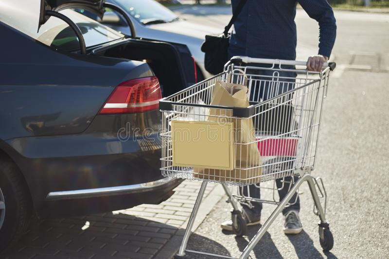 Främre sikt av en man med en shoppingvagn bak en bil med den öppnade stammen utanför en supermarket royaltyfria bilder