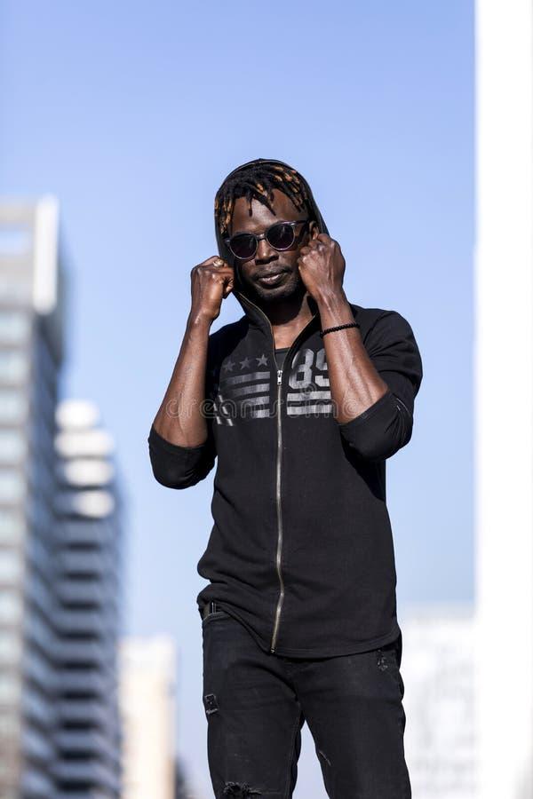 Främre sikt av en ung svart afrikansk man som bär tillfällig kläder och solglasögon som står i gatan, medan se kameran i a royaltyfri fotografi