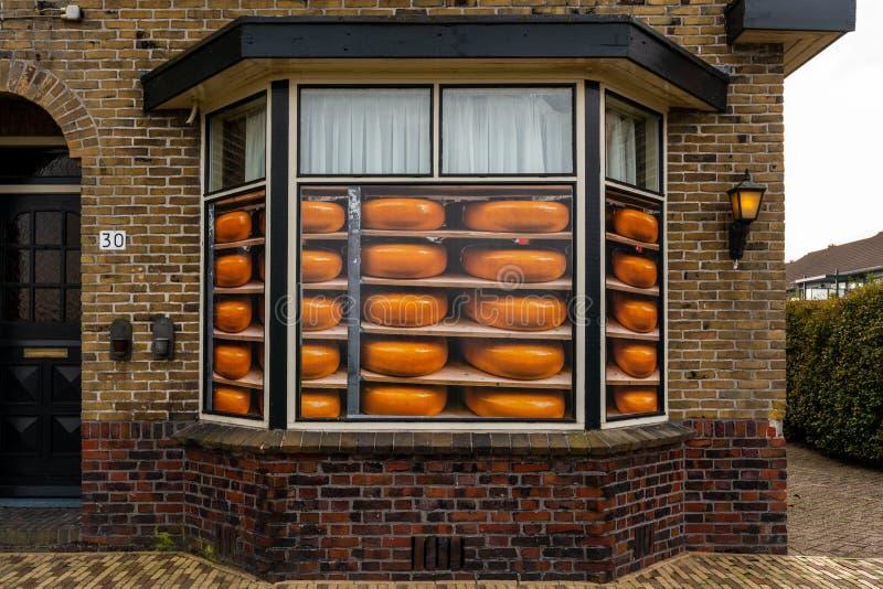 Främre sikt av ett ostlagerfönster med runda gula ostklistermärkear, brun tegelstenbyggnad royaltyfri foto