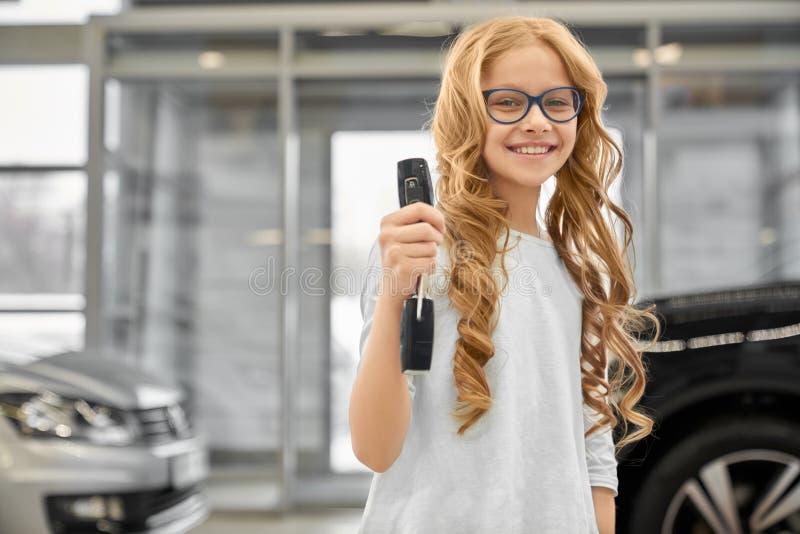 Främre sikt av gladlynta tangenter för flickavisningbil i automatisksalong arkivfoton