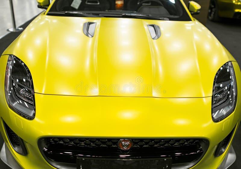 Främre sikt av gul matt Jaguar F-typ kupé S 2017 Bilyttersidadetaljer arkivbild